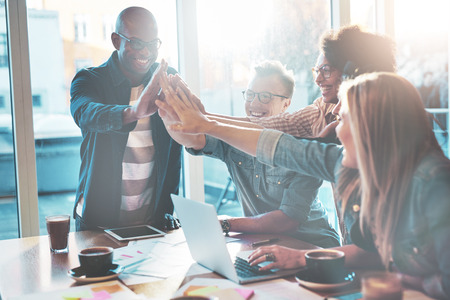 Gelukkige jonge ondernemers in vrijetijdskleding bij koffietafel of in bedrijfsbureau die hoge vijfen aan elkaar geven alsof succes vieren of nieuw project beginnen