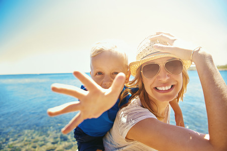 Young smiling mother with little boy on back that outstretching hand at camera on background of seaside. Stock Photo
