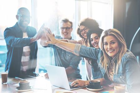 互いに与えること高い成功を祝うまたは新規プロジェクトを開始、ポーズ、カメラ目線の 5 つのカフェで若い起業家のグループ