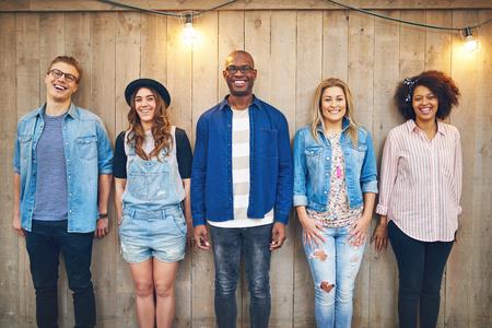 personas de pie: Cinco jóvenes, hombres y mujeres en el desgaste casual de pie todavía en una fila en la pared sin pintar de madera, sonriendo y mirando a la cámara