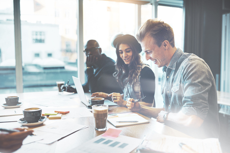 Diverses multiracial junges Business-Team in einem hohen Schlüssel Büro sitzt an einem Laptop arbeitet und Papierkram mit glücklichen Lächeln