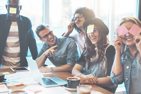 Groep van mooie jonge mensen bij cafe tafel met laptop met plezier samen te spelen de naam spel met kleverige nota's aan hun voorhoofd, lachen Stockfoto