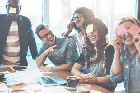 Groupe de jeunes gens belle à la table de café avec un ordinateur portable s'amuser ensemble en jouant un jeu de nom avec des notes collantes sur leur front, rire