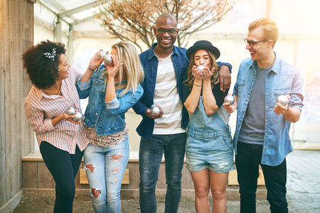 goofing: Group of beautiful young people in casual wear having fun in petanque game club standing together and posing at camera, laughing