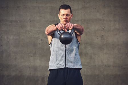 outstretching: Young sportive concentrated man outstretching hands forward with heavy kettlebell and looking at camera.