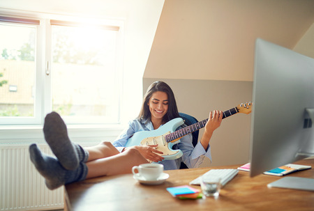 Cute single young laughing woman with feet on table while playing electric guitar in front of computer monitor Stock Photo