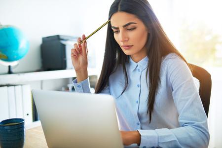 Jonge Aziatische zakenvrouw fronsen van bezorgdheid als ze probeert te begrijpen iets dat ze op haar laptop computer leest krabben haar hoofd met haar potlood in verbijstering