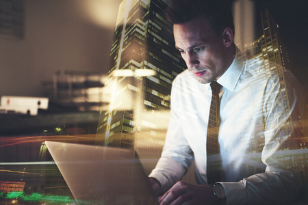 ビジネス人のコンピューターに取り組んで、彼の机に座って集中してください。