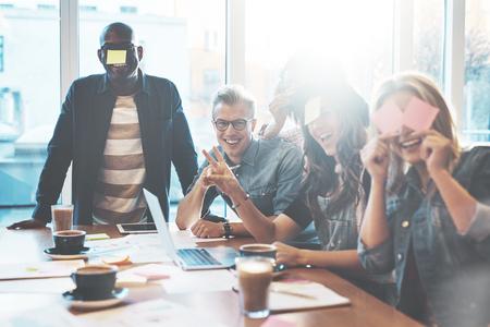 Groep jonge mensen in café met leuke speelnaam game met plakbriefjes aan hun voorhoofd, tegen een breed licht venster Stockfoto