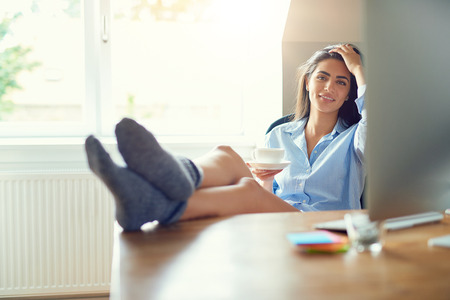 Relaxing after a hard day at her home office, a single young entrepreneur sits back with feet on desk while holding a coffee cup Stock Photo
