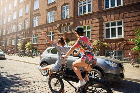 Trendy young women riding along a cobbled residential street on a bicycle waving on a hot summer day