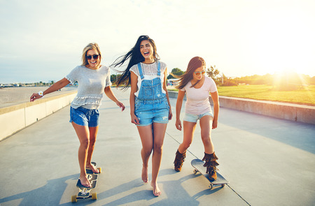 unwinding: Three active pretty young woman on a day at the seaside enjoying their summer vacation skateboarding along a beachfront promenade at sunrise laughing and smiling Stock Photo
