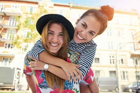 Teen in striped hair and tied back hair on shoulders of happy friend in hat laughing at urban setting
