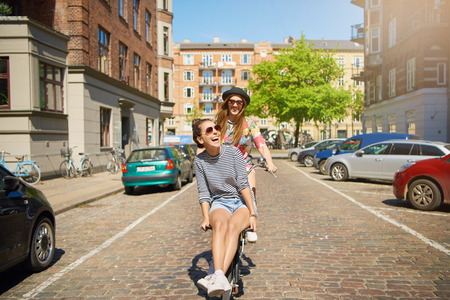 Teenage female in black hat riding on bike with friend outside going in wrong direction on street Stock Photo