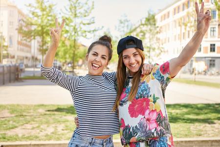 彼らはカメラに向かって笑みを浮かべて夏の暑い日の静かな都市通りに腕をスタンドに撮るを作るとする幸せの若い女子学生 2