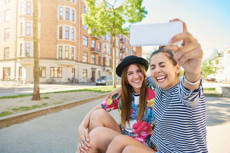 Candid image of a laughing young woman taking a selfie with her trendy young friend as they sit together on the curb in a quiet urban street Stock fotó