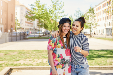 Cute young girlfriends posing arm in arm in trendy summer clothes grinning happily at the camera in an urban street Stock Photo