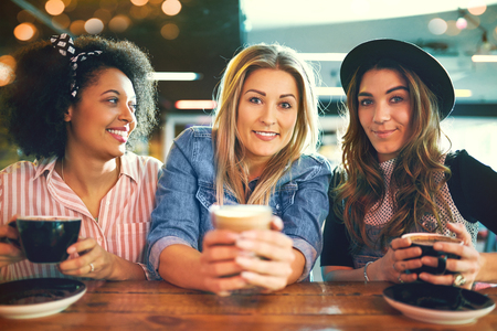 Three trendy multiracial young women enjoying coffee together in a cafeteria sitting in a row looking at the camera with friendly smiles