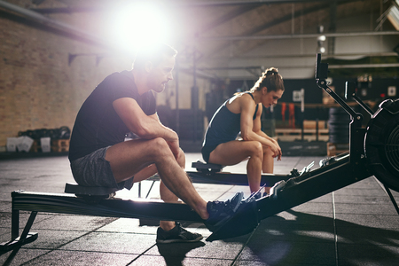 Young man and woman having rest after hard workout on rowing machines in gym. Stock Photo