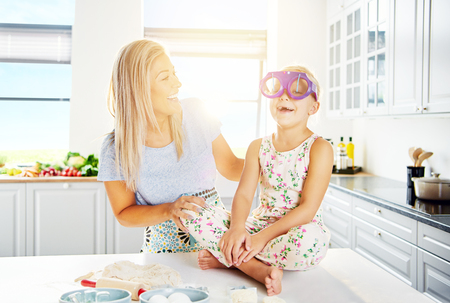 Woman laughing as child wears silly glasses while seated on table beside bread dough ingredients Stock Photo