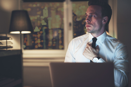 Serious businessman thinking sitting at office at night working overtime, solving a problem
