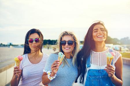 그들이 여름 휴가에 테이크 아웃 아이스크림 콘을 즐기고 행복하게 미소 짓는 행렬에 서있는 산책로에 세 즐거운 젊은 여자 친구