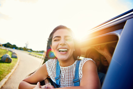 Pretty woman in speeding car smiles at camera while friends laugh in seat behind her