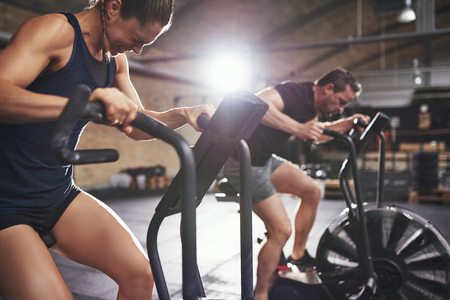 Young man and woman in hard efforts riding cycling machines in modern light gym.