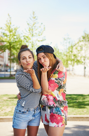 Two cute sexy women in trendy summer clothes standing arm in arm blowing seductive kisses over the palms of their hands at the camera Stock Photo