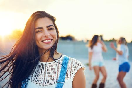 일몰 동안 해변에 배경에서 춤 친구의 쌍으로 웃는 여자의 여름 현장 스톡 콘텐츠