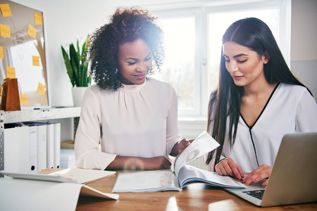Two young businesswomen working on a report or paperwork together at an office table in a close up high key view with sun flare
