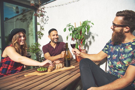 merrymaking: Bearded man toasts with his friends and smiles while seated outside as the sun shines onto their apartment patio