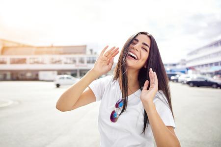 Lachende Frau in der weißen kurzen Hülsenbluse mit Sonnenbrille auf Hemd mit den Händen oben bei der Stellung in der Straße mit Kopienraum im Hintergrund Standard-Bild