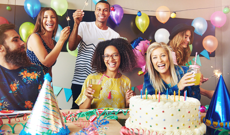 merrymaking: Six young adults celebrating a birthday party while holding drinks as they sit around a table with cake and party hats