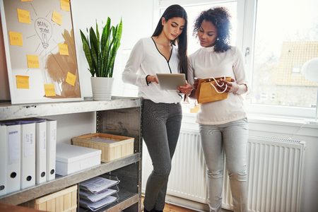 Two young entrepreneurs discussing packaging together as they stand working on a design or branding on a tablet for their small business, shelves of binders in the foreground