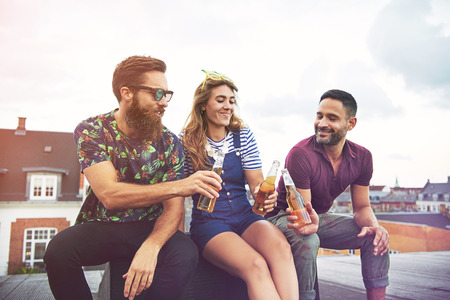 merrymaking: Cheerful group of friendly adults drinking and toasting with beer bottles on roof outdoors with copy space in sky Stock Photo