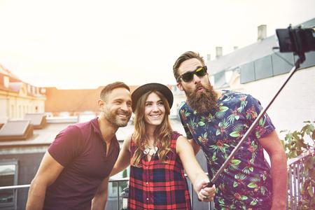 友人のグループ テラスの柵のそばに立って、彼らはデバイスを使用して写真を撮ると笑顔