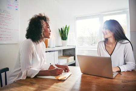 높은 키 사무실에서 책상에 앉아 그들의 새로운 시작 비즈니스의 전략을 계획하는 토론 데 두 젊은 매력적인 multiracial 비즈니스 동료 스톡 콘텐츠