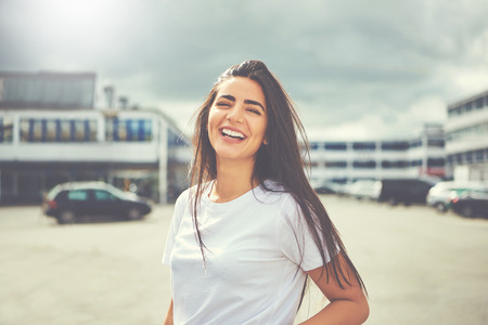 Laughing woman in white blouse and long hair standing in the middle of large parking lot outdoors