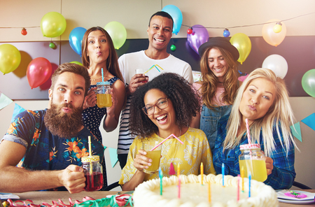 merrymaking: Six diverse group of friends at party sitting at table in front of large birthday cake while holding drinks Stock Photo
