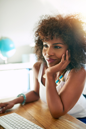 Young pretty afro american woman using small business computer and smiling on blurred inside background Stock Photo