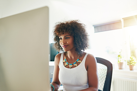 Smiling young female African entrepreneur sitting at her desk in her home office working on a large desktop monitor, high key background