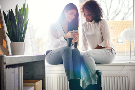 Smiling young women sitting together on a bright windowsill texting a phone message on their mobile with happy smiles