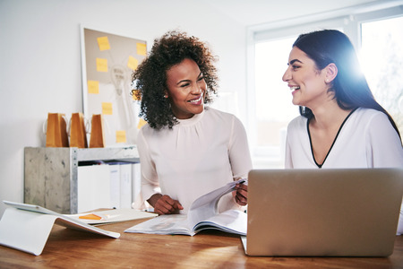 Two happy attractive young multiracial businesswomen laughing together as they sit working in a bright high key office on paperwork and a laptop computer