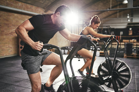 Young man in backlit and woman riding in hard efforts on cycling machines in modern spacious gym.