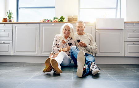 Laughing mature couple holding wine in kitchen while seated on tiled floor. Copy space around them.