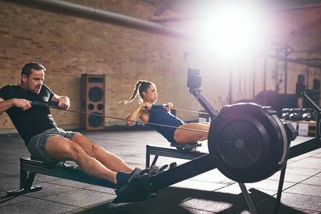 Deux jeunes sportifs s'entrainent sur des machines à ramer dans une salle de sport spacieuse et lumineuse. Banque d'images