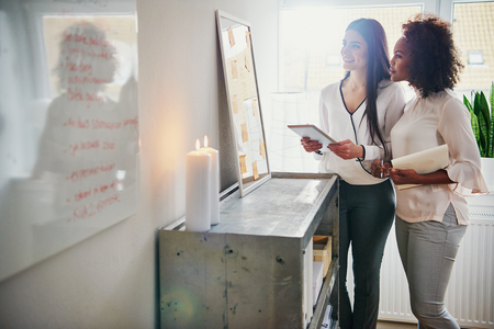 Two businesswomen holding a tablet and paperwork standing looking at their memo board with new ideas and planning in the office as they discuss their small business, high key with copy space Фото со стока