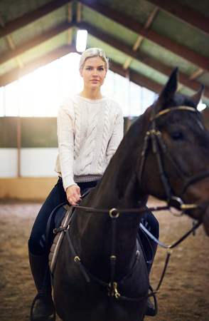 Blonde?female sitting astride dark horse in riding hall. Stock Photo - 75315598