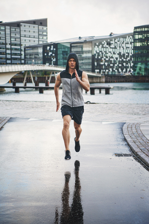 sleeveless hoodie: Man athlete in sleeveless hoodie exercising jogging outdoors in the city on rainy day. Front portrait with bridge and modern buildings in background Stock Photo